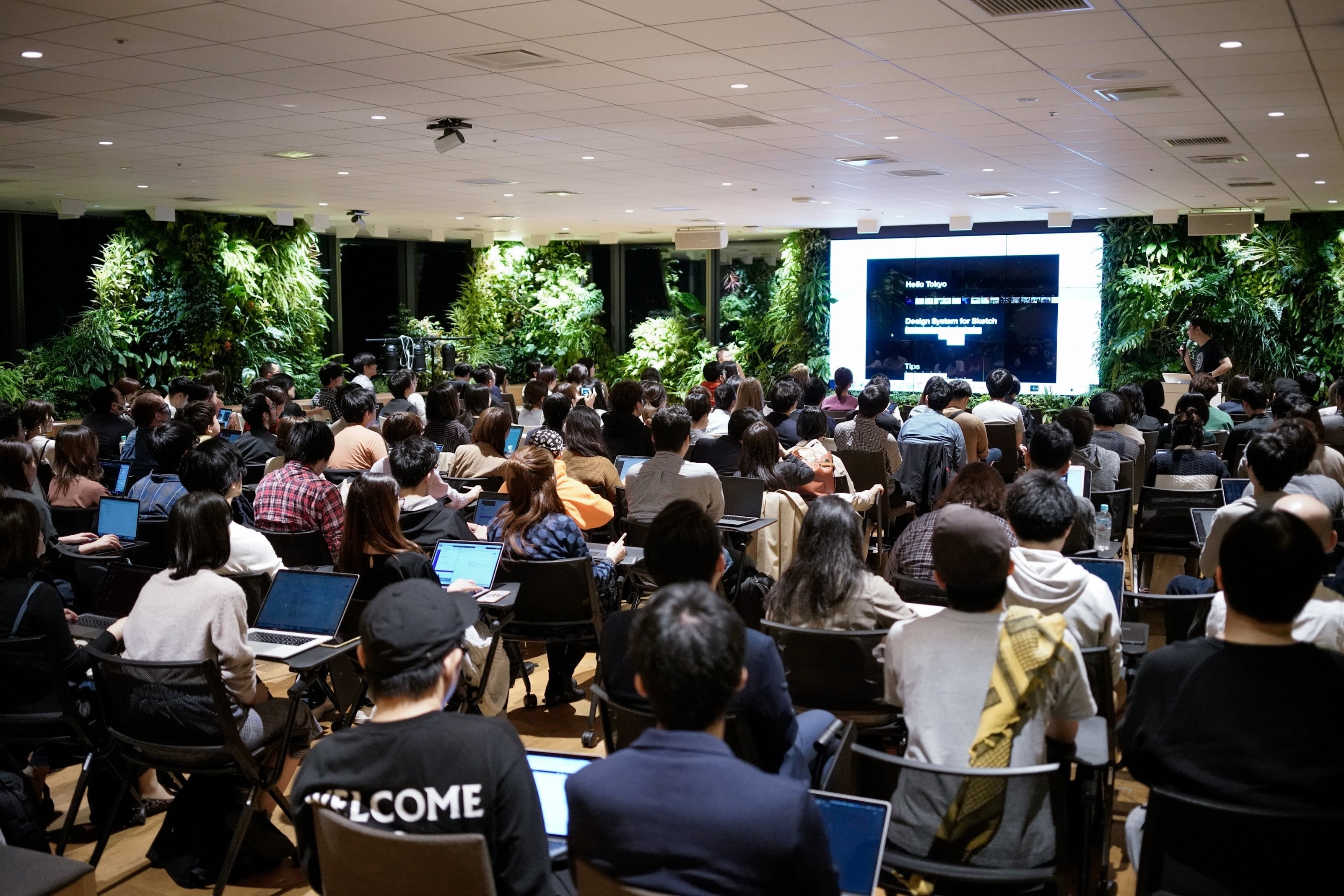 A photo from a meetup in Tokyo with almost 100 people watching a presentation.